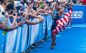 A US Olympian running with a flag, getting congratulated by fans.